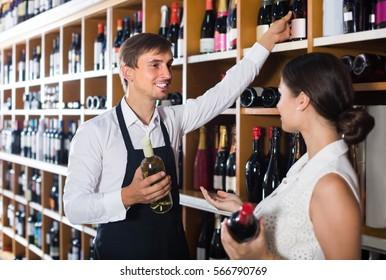 portrait of positive russian male seller in uniform showing bottle of wine to female customer in wine shop