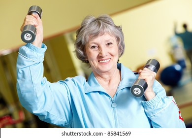Portrait of positive senior woman lifting dumbbells, looking at camera and smiling