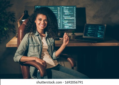 Portrait of positive skilled afro american girl web designer engineer sit chair enjoy her night company data work hold glasses in workplace workstation