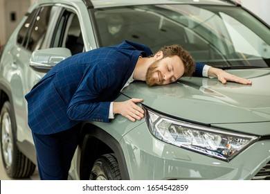 portrait of positive smiling happy man buyer in dealership, stand happily posing next to new car, wearing formal suit. funny bearded man hug new auto