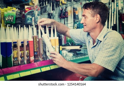 Portrait of positive smiling male customer selecting sealant bottle in housewares department