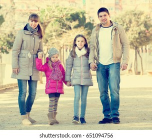 Portrait of positive smiling young family with kids walking in the street