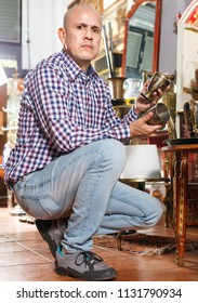 Portrait of positive   successful owner of antiques shop among vintage things