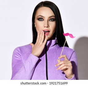 Portrait of positive surprised pretty brunette woman in purple longsleeve touching mouth holding decorative pink mustache in hand looking at camera over white background. Playful mood concept
