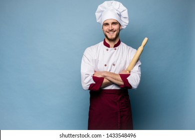 Portrait of positive toothy chef cook in beret, white outfit having tools in crossed arms looking at camera