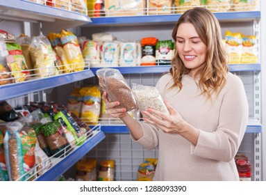 Portrait of positive woman buyer holding assortment of grocery food store