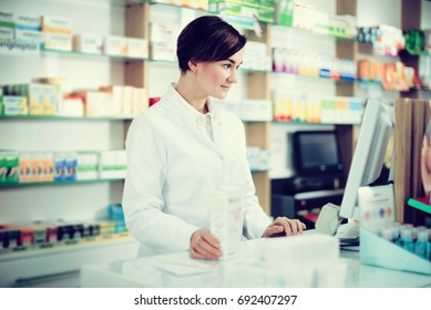 Portrait of positive woman pharmacist ready to assist in choosing at counter in pharmacy