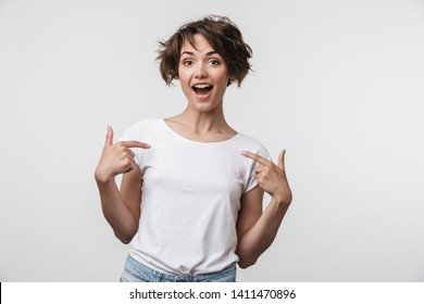 Portrait of positive woman with short brown hair in basic t-shirt rejoicing and pointing fingers at herself isolated over white background