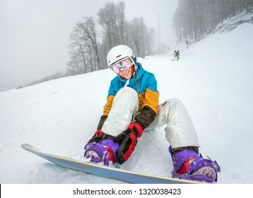Portrait of positive woman snowboarder, fastened to snowboard on background of falling snow with poor visibility weather in high mountains of Caucasus at Krasnaya Polyana