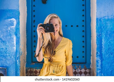 Portrait of positive woman using retro equipment for taking pictures during summer trip for exploring Chaouen berber culture, happy female tourist with technology enjoying international vacations