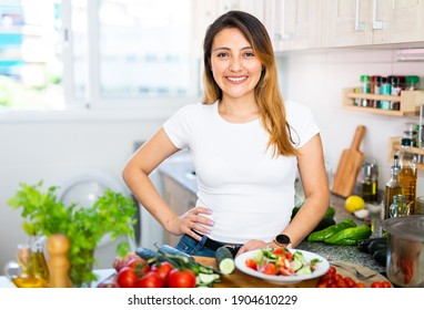 Portrait of positive woman with vegetables at kitchen top