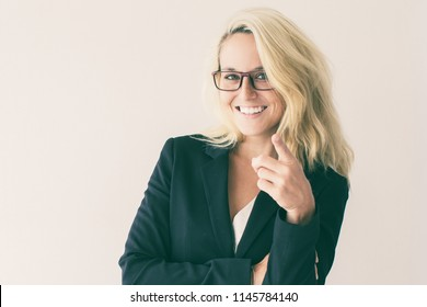Portrait of positive young Caucasian businesswoman wearing costume and glasses pointing at camera and smiling