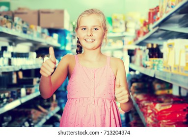Portrait of positive young girl thumbs up in the supermarket