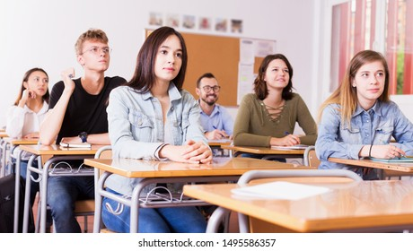 Portrait of positive young girl who is sitting at the desk in the classroom.