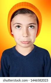 portrait of pouting young boy with big head on orange background