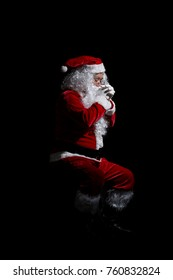 Portrait of praying Santa Claus isolated over a black background.