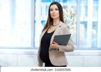 Portrait of pregnant businesswoman - Confident pregnant woman in business dress working in office, holding tablet.