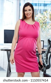 Portrait of pregnant businesswoman - Happy pregnant woman in pink business dress working in office.