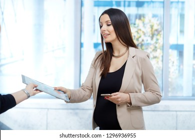 Portrait of pregnant businesswoman - Happy pregnant woman in business dress working in office, holding tablet.