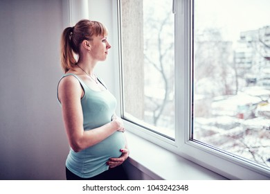 Portrait of pregnant mature woman standing near the window and caresses her belly.