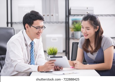 Portrait of pregnant woman with doctor in clinic