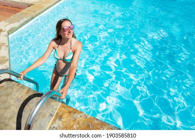 Portrait of a pregnant woman enters the swimming pool view from above wearing shades