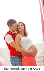 Portrait of pregnant woman with husband hugging her tummy