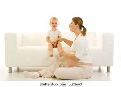 Portrait of a pregnant young mother with her toddler child. Isolated view with white emphasis.