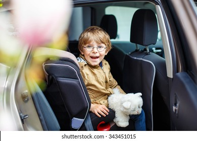Portrait of preschool little kid boy with glasses sitting in car. Child in safety car seat with belt and toy. Safe travel with kids and traffic laws concept.