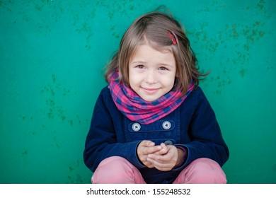 Portrait of preschooler girl sitting near wall
