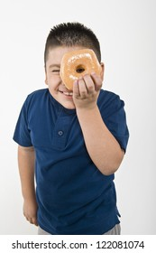Portrait of a preteen boy looking through donut isolated over white background