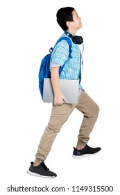 Portrait of a preteen boy student posing walk on the stairs while carrying a laptop, isolated on white background