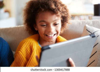 Portrait of pre-teen girl looking at tablet computer screen laughing, close up, selective focus