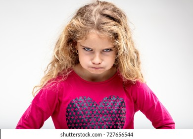 Portrait of preteen sulky girl making angry face against plain background