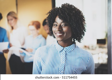 Portrait of pretty african american business woman with afro smiling at the camera.Coworking team on background in modern office. Horizontal,blurred