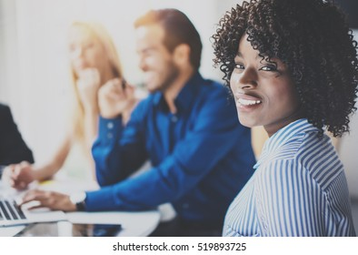 Portrait of pretty african american business woman with afro smiling at the camera.Coworking team in brainstorming process on background in modern office. Horizontal,blurred