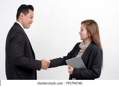 Portrait of pretty Asian businesswoman with a digital tablet shaking hands with businessman to seal a deal with his partner on a white background
