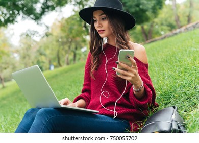 Portrait of a pretty asian girl in earphones using mobile phone and laptop computer while sitting on grass outdoors
