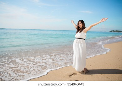 A portrait of pretty asian pregnant woman enjoying the beach with open arms