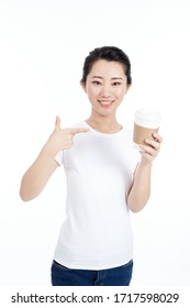 Portrait of a pretty asian woman holding takeaway coffee cup isolated over gray background