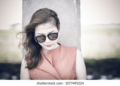 Portrait of pretty Asian woman in red suit with reflection in sunglasses, process in vintage style