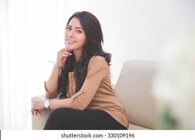 portrait of pretty asian woman sitting on the couch looking at the camera