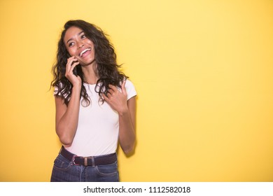 portrait of pretty asian woman talking on mobilephone with hand gesture on yellow background