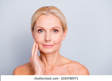 Portrait of pretty, attractive, charming, naked, nude woman touching her  perfect skin, isolated on grey background,  after peeling, lotion, mask, perfection, wellness, wellbeing, hydration concept