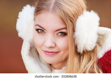 Portrait of pretty attractive fashionable woman in fall forest park. Gorgeous young girl in white fur earmuffs. Autumn winter fashion.