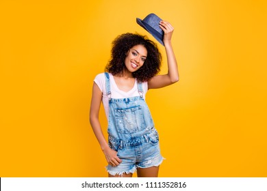 Portrait of pretty attractive girl in casual outfit taking off hat looking at camera isolated on yellow background. Greeting vacation weekend holiday concept