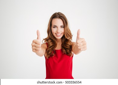 Portrait of a pretty attractive woman in red santa claus outfit showing thumbs up with two hands over white background