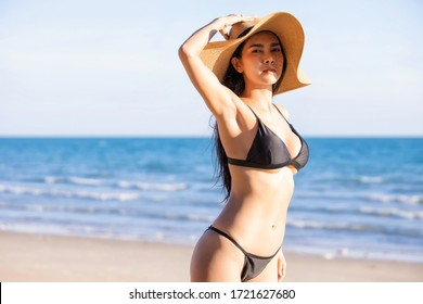 Portrait of pretty beautiful fashion woman sexy body in black bikini in summer on the sand on the beach of tropical island.