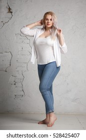 Portrait of a pretty big blonde in a white shirt on a gray background in full length.
