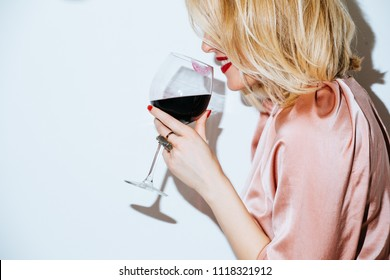 Portrait of pretty blonde Caucasian woman holding glass of red wine.